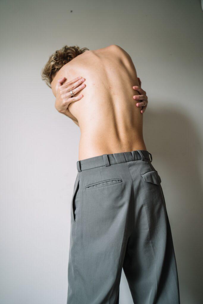 Mujer con espalda descubierta, entrelazando sus brazos de espalda