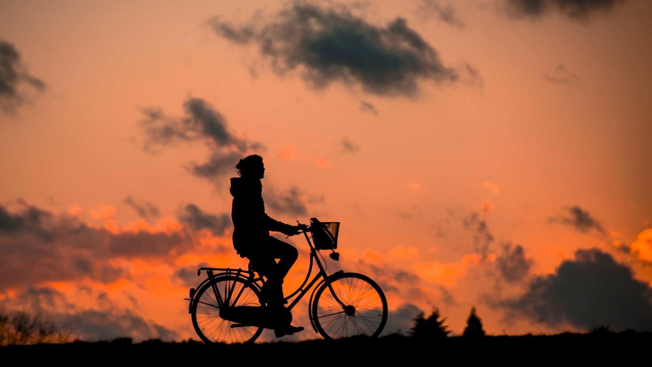 Silueta de hombre en bicicleta al atardecer. Cosas que hacer antes de que haga calor