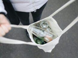 manos sostienen bolsa de tela con botellas de vidrio para reciclaje; negocios sostenibles