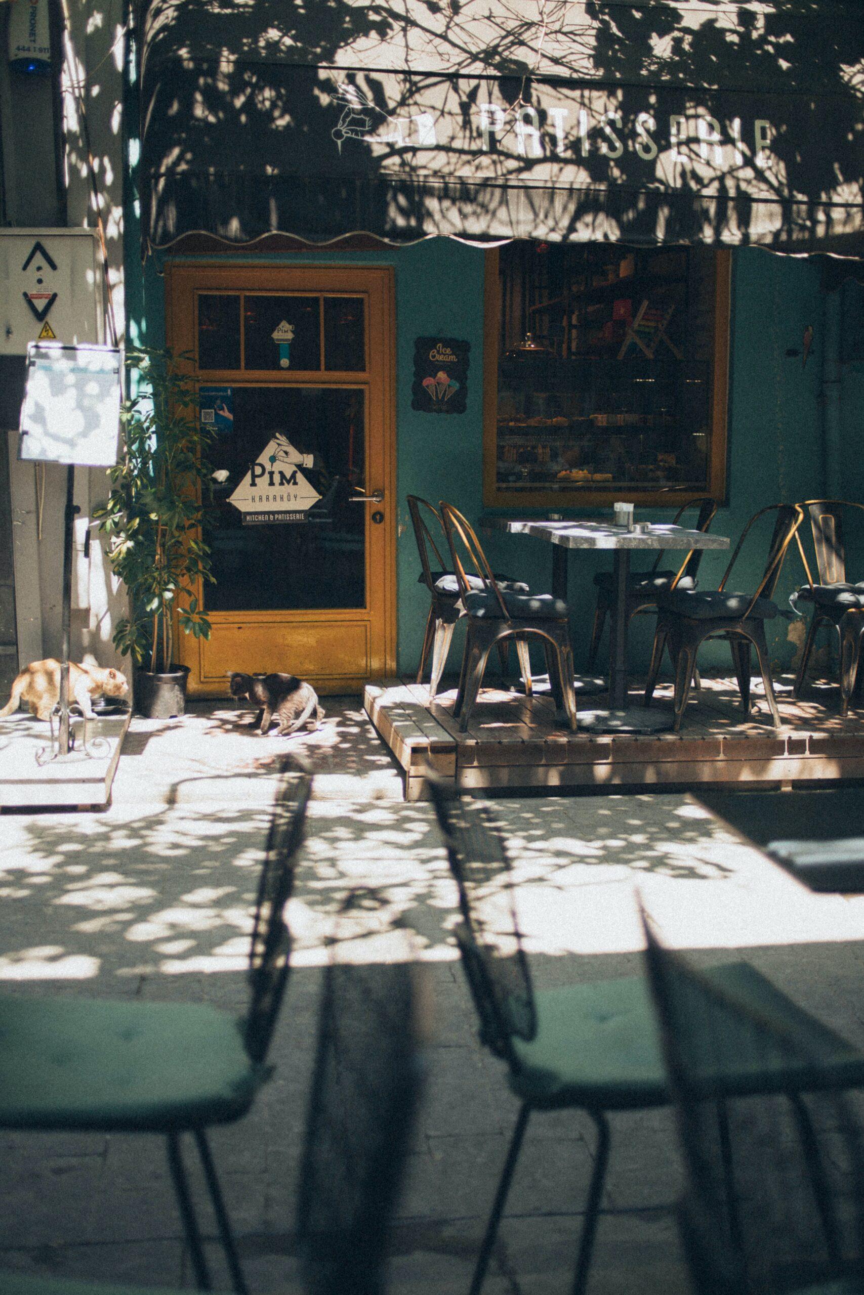 Exterior de café, color azul, mesas en exterior y día soleado