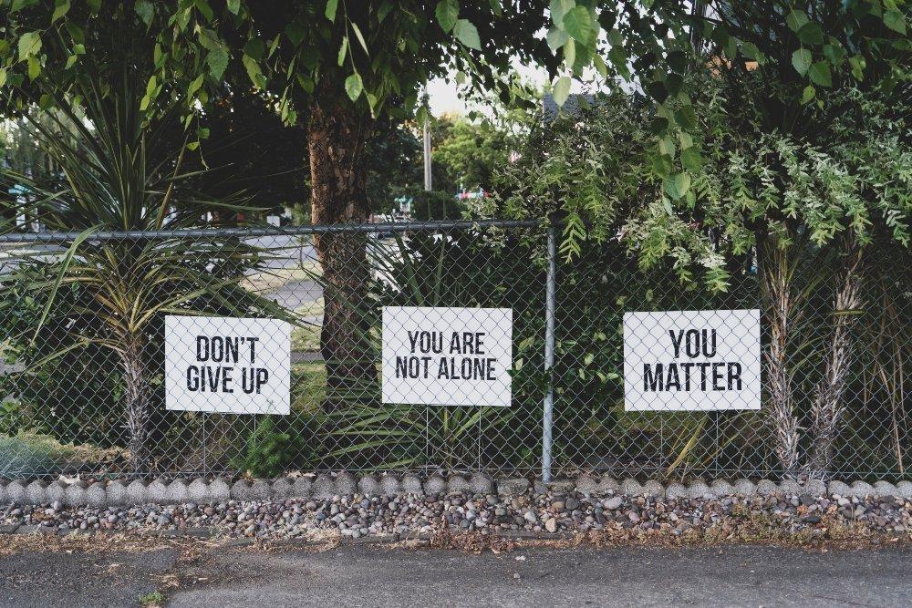 carteles con frases de motivación en inglés sobre una reja frente a unas palmeras y árboles; los carteles dicen Don't Give Up, You Are Not Alone y You Matter.
