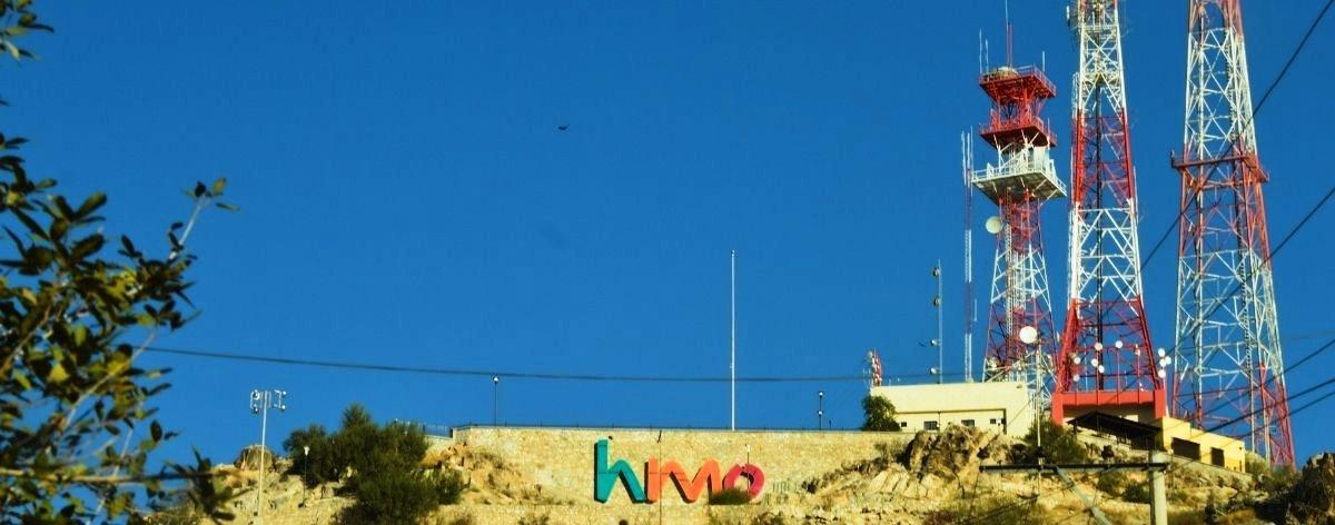 Fotografía del Cerro de la Campana en Hermosillo, Sonora, con antenas color rojo con blanco y letras que de color azul, naranja y rosa que dicen HMO