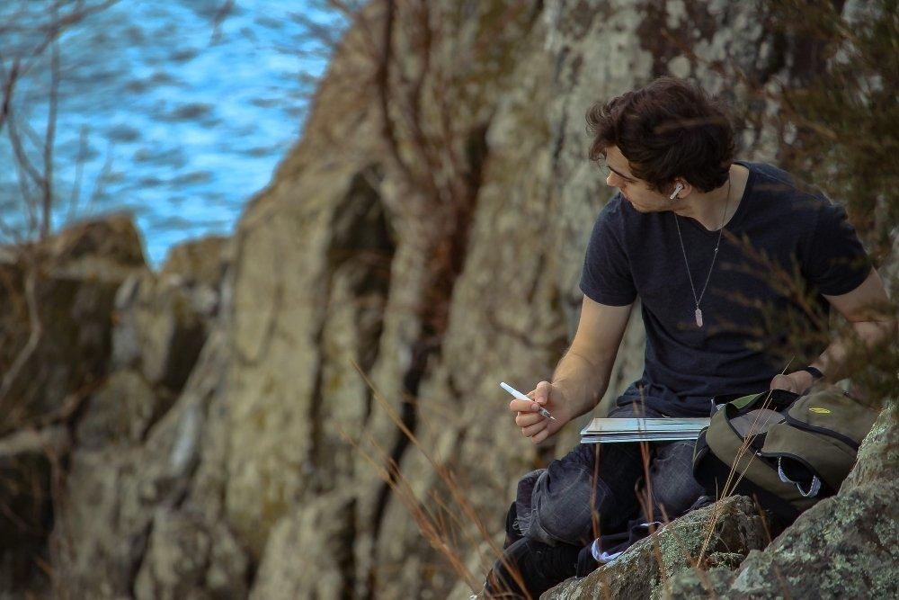 hombre sentado sobre un roca escribiendo y oyendo musica