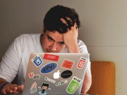 hombre sentado tocándose la cabeza con la mano mientras mira su computadora gris con stickers de colores; hombre con estrés por trabajo