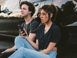 hombre y mujer escuchan musica con audifonos