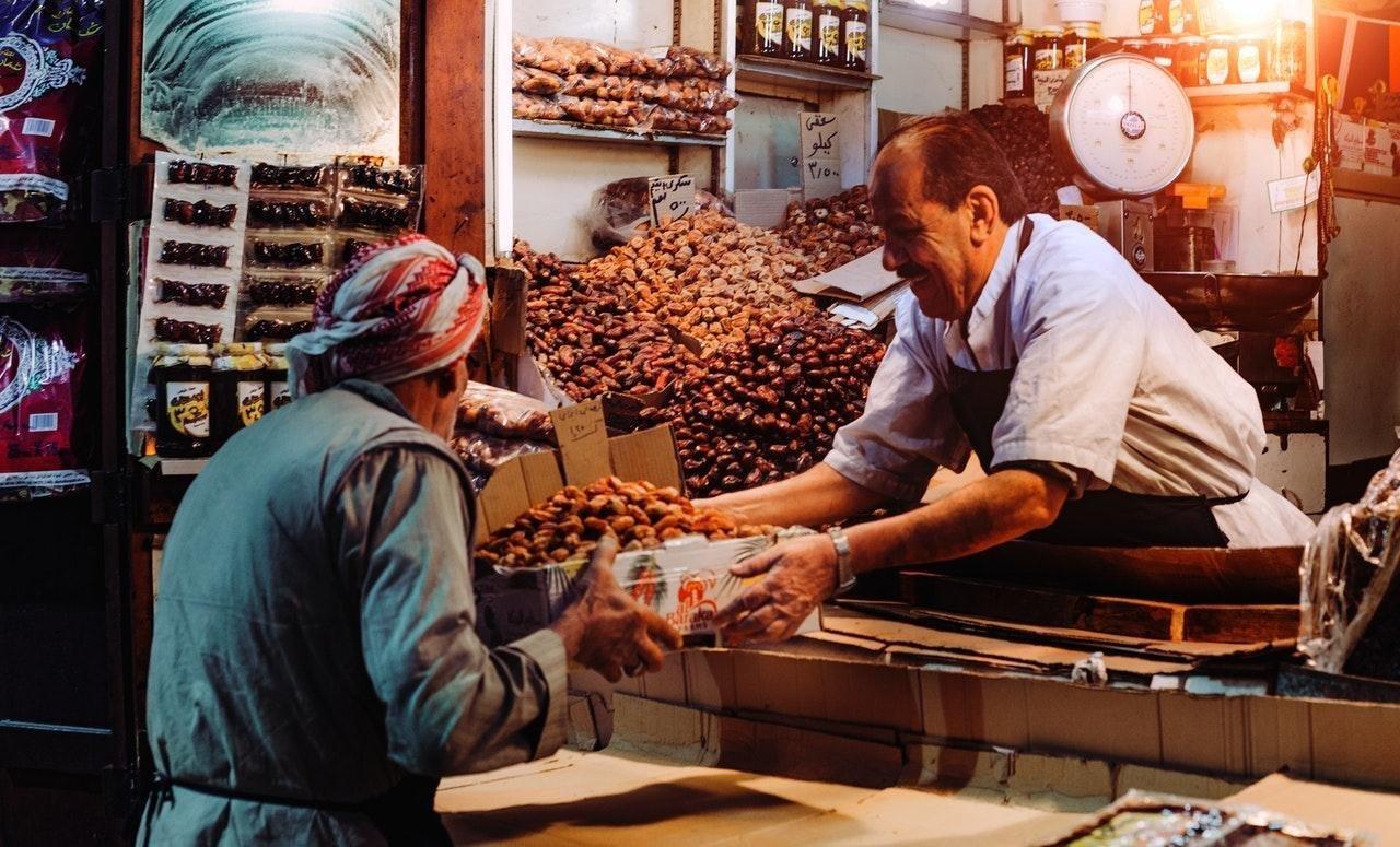 hombre de cabello oscuro, camisa blanco y mandil negro, le entrega a otro señor con un pañuelo en la cabeza una caja con dátiles. Ambos están en un lugar donde venden frutos secos y especias. Consumo local