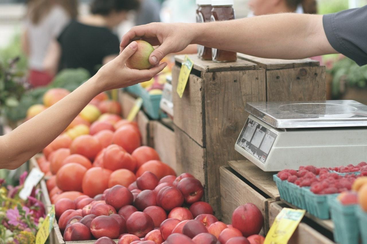 dos personas sostienen una mana color verde con rojo en un mercado al aire libre donde hay manzanas, tomates y frambuesas; consumo local