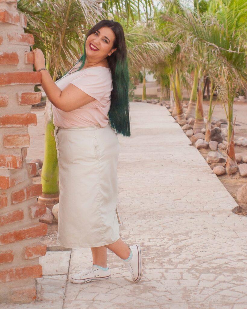 Mujer con cabello muy largo color café oscuro y verde, con una blusa color rosa pastel y falta color crema