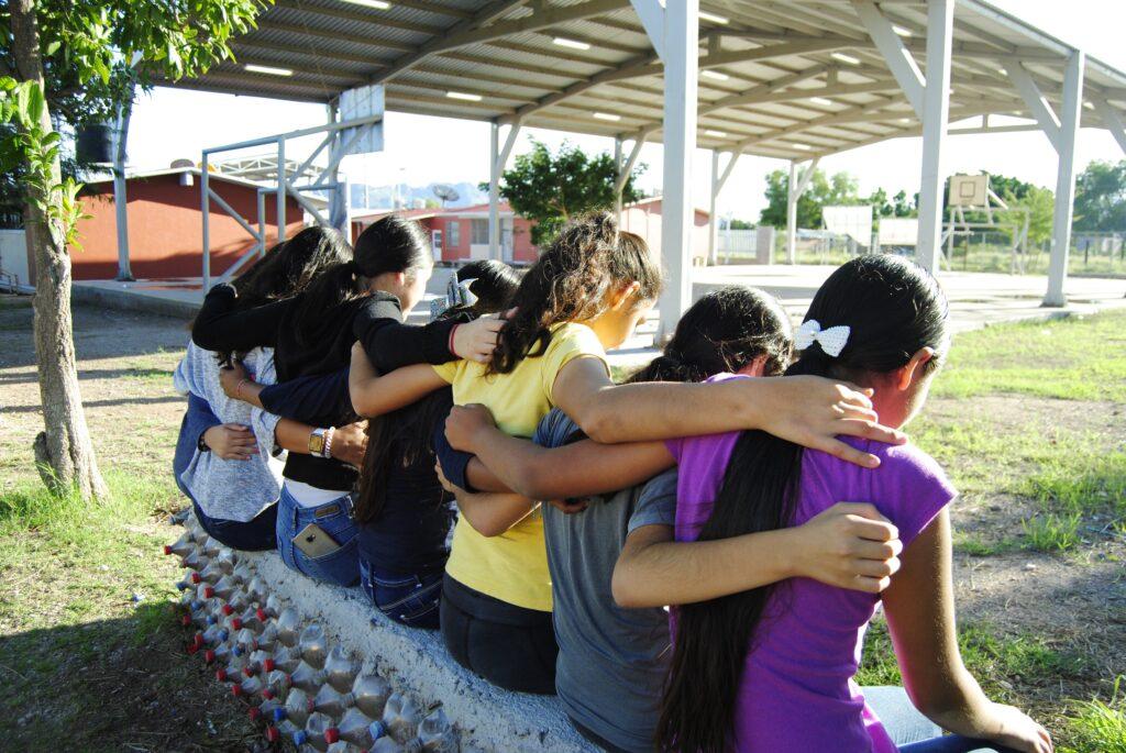 Abrazo grupal de mujeres jóvenes de espalda, la primera tiene una camiseta color morado, la segunda gris, la tercera amarilla, la cuarta y quinta negra y sexta color gris claro