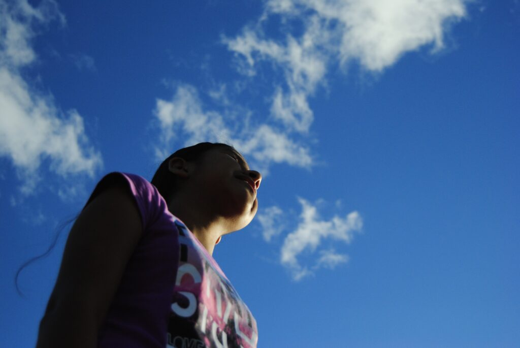 Mujer joven con blusa color morada de fondo cielo azul con nubes blancas