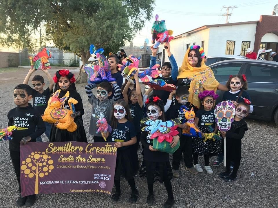 Grupo de niños y niñas vestidos de catrina todos de negro y con cara pintada, presentando trabajos artísticos.
