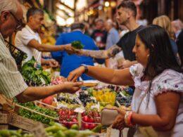 personas comprando frutas y verduras en un mercado al aire libre
