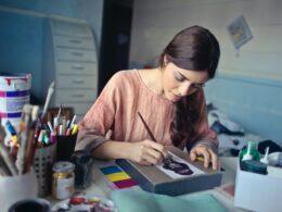 mujer de cabello largo y blusa rosa pinta con un pincel sobre un lienzo, a su lado hay colore sy pinturas dentro de un bote; diseño gráfico sustentable