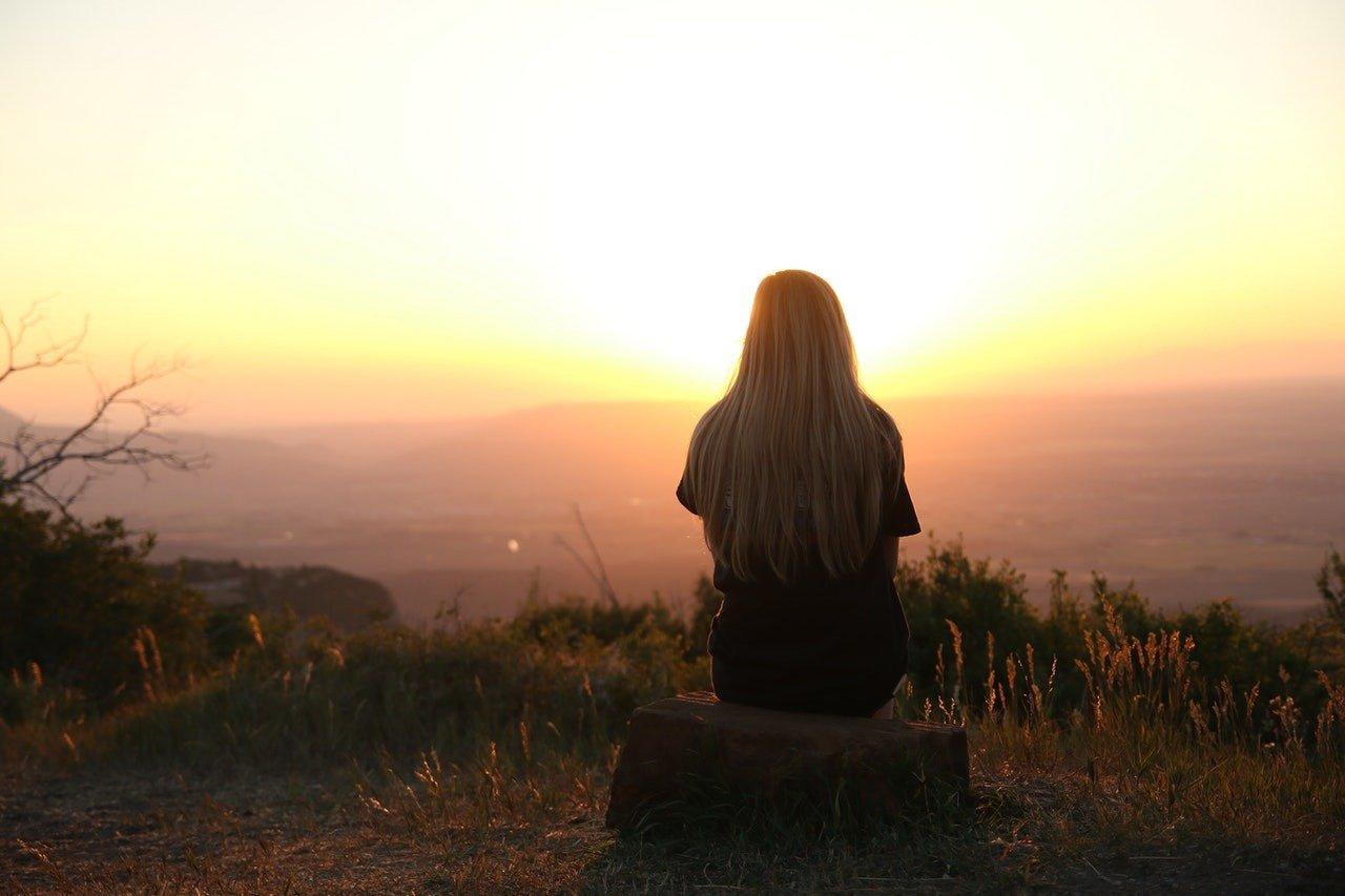 Mujer con cabello muy largo, viendo al horizonte el atardecer de color naranja-amarillo: bienestar psicológico