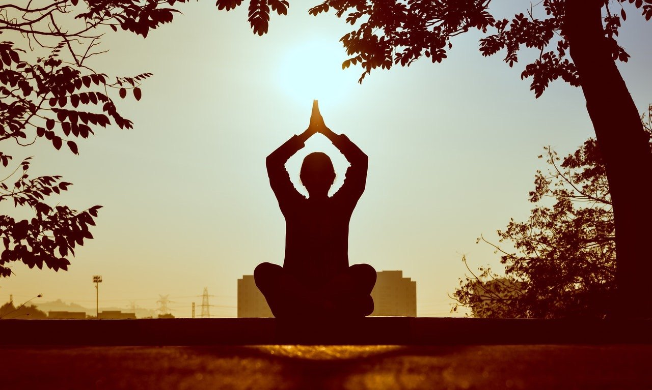 Mujer juntando manos, elevadas encima de la cabeza, sentada en una piedra