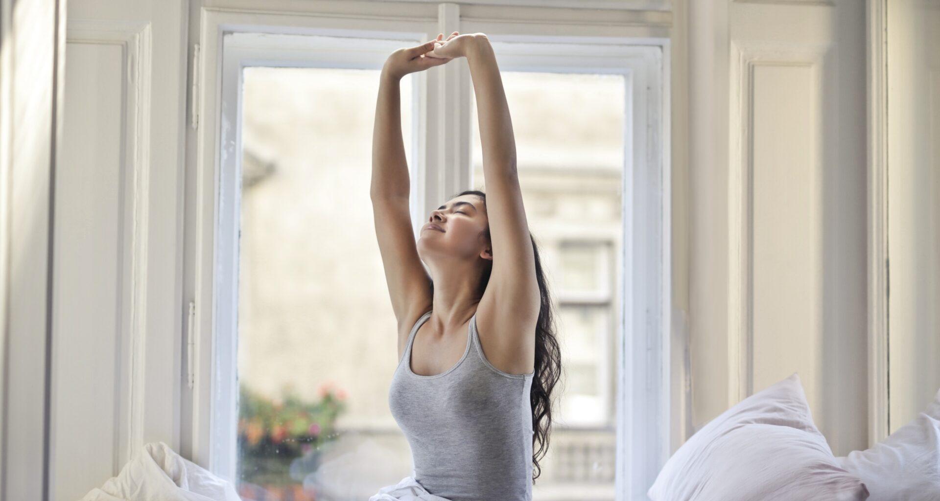 mujer vestida de gris estira los brazos sobre su cabeza mientras está sentada en su cama