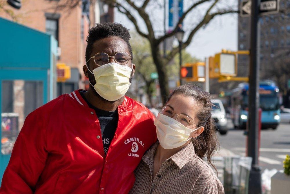 Hombre con chaqueta roja, gafas y mascarilla amarilla junto a una mujer con gafas, camisa beige y café con mascarilla blanca; dos personas en la calle usando cubrebocas, en la parte de atrás hay un autobús de color azul y una camioneta color blanco.