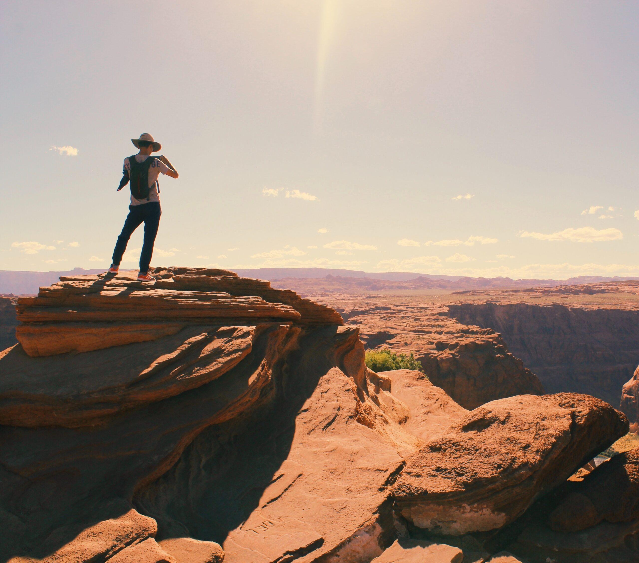 Hombre en cima de montaña, de espaldas, durante día cálido
