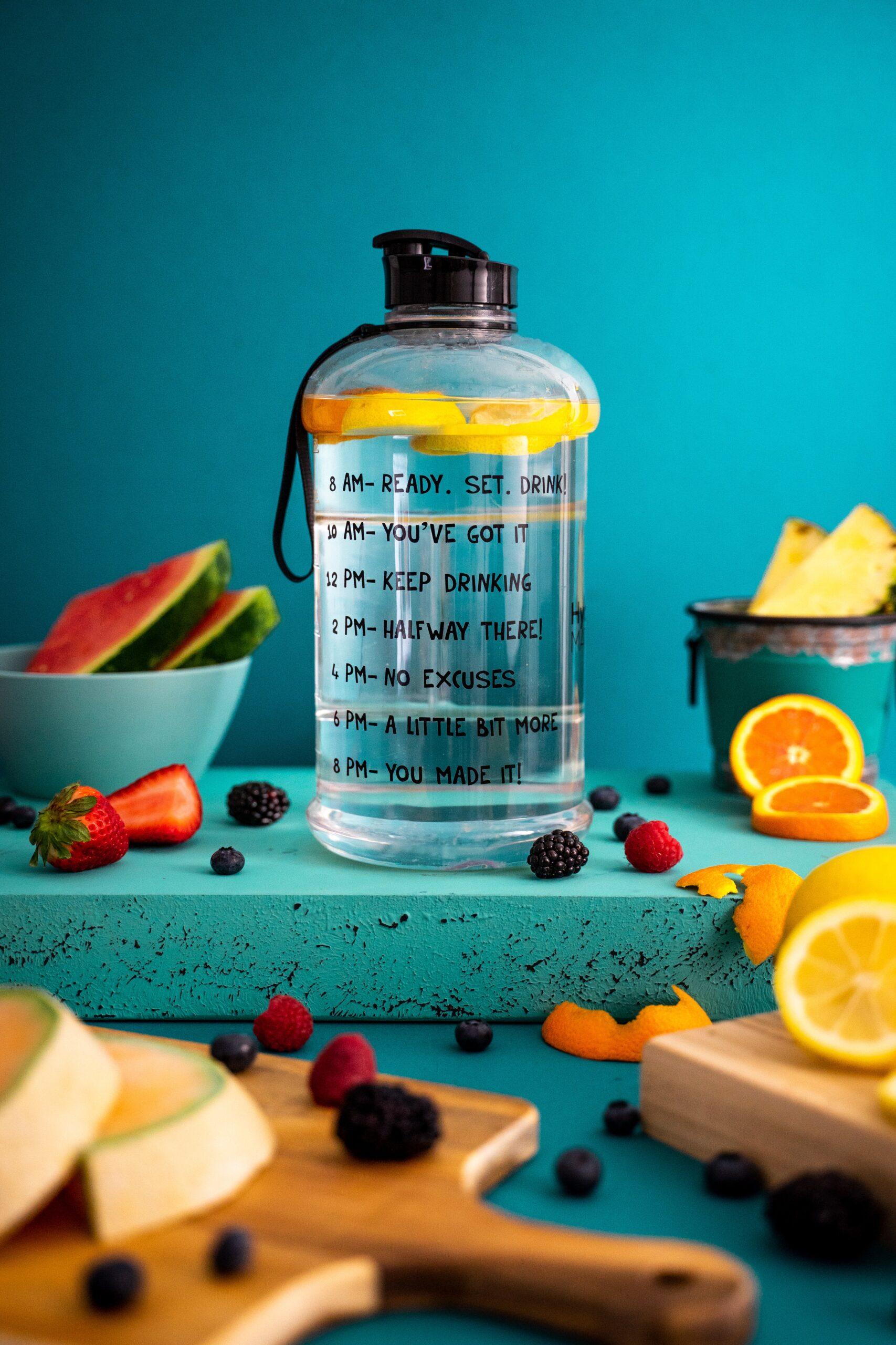 Botella de agua con rodaja de naranja dentro; home office