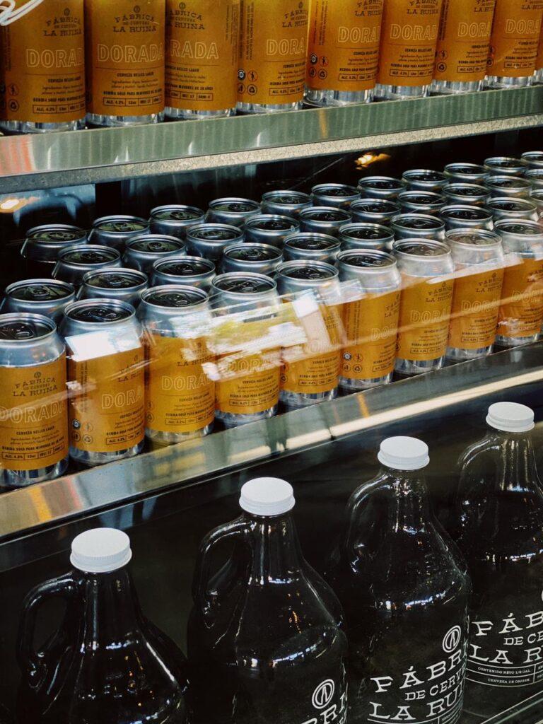 Refrigerador lleno de latas de cerveza color plateadas con etiqueta color naranja. En la parte de abajo del refrigerador se encuentran unos galones de cerveza de vidrio color ambar con tapa color blanca.