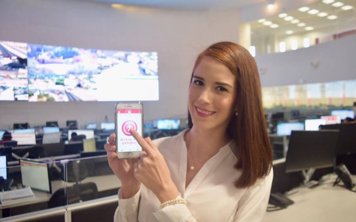 Cassandra López Manzano mostrando App Mujeres Seguras en su teléfono blanco. Detrás hay monitores de computadoras