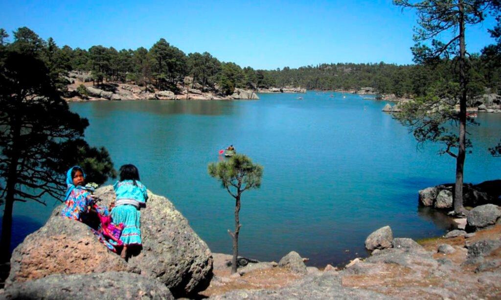 Paisaje de una laguna con arboles grandes. En la orilla de abajo se observan piedras gigantes y en ellas se encuentran dos niñas con vestido color azul.