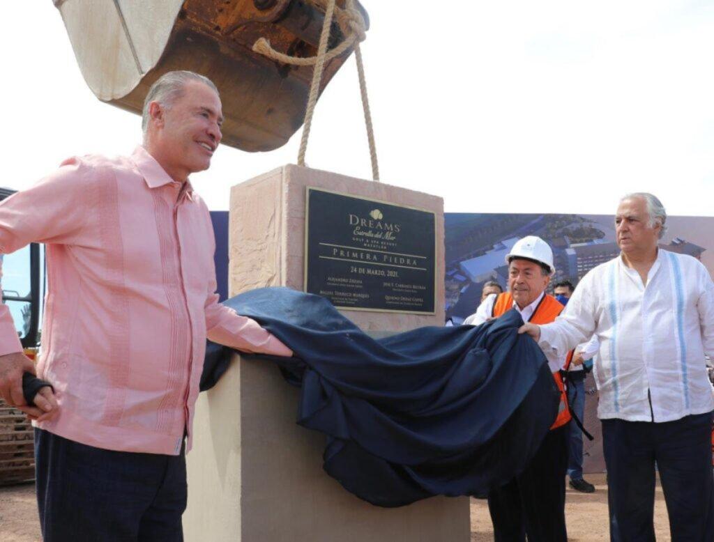 Tres hombre sosteniendo una manta de color azul marino. El hombre del lado izquierdo tiene una camisa de manga larga color rosa y pantalon color negro. El hombre del lado derecho tiene una camisa color blanca con franjas azules y pantalon negro.