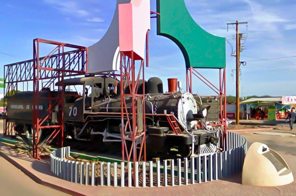 Monumento de ferrocarril de Empalme, color negro con letras color blanco y en la parte de enfrente una estructura color roja. En la parte de arriba tres figuras de color roja, verde y blanco.