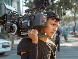Hombre con camisa y gorra color negra cargando camara de video