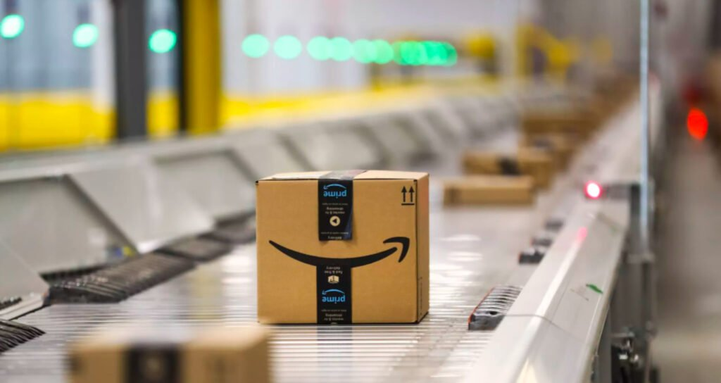 Caja de cartón con una flecha de color negra en medio, característica del logotipo de Amazon. La caja se encuentra en una maquina de metal.