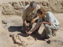 Pareja de mujer y hombre vestidos de color arena, observando una pieza arqueológica