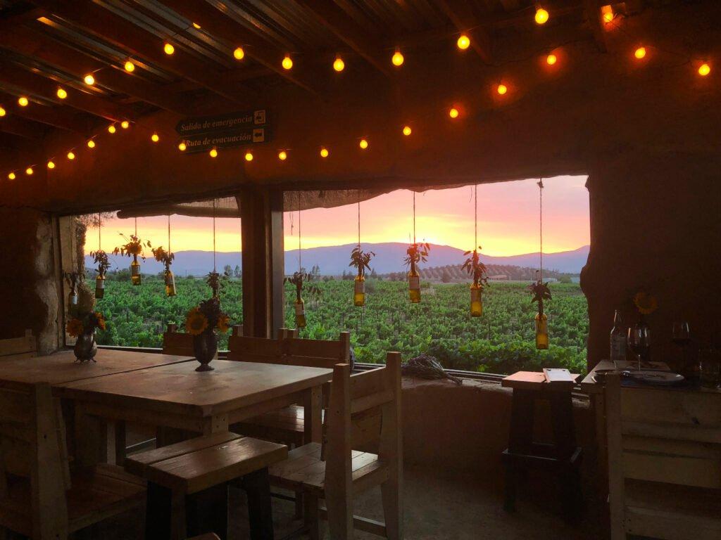 Restaurante con ventanas grandes abiertas en donde se ve un atardecer de color amarillo con rojo. En las ventanas hay colgadas botellas con plantas.