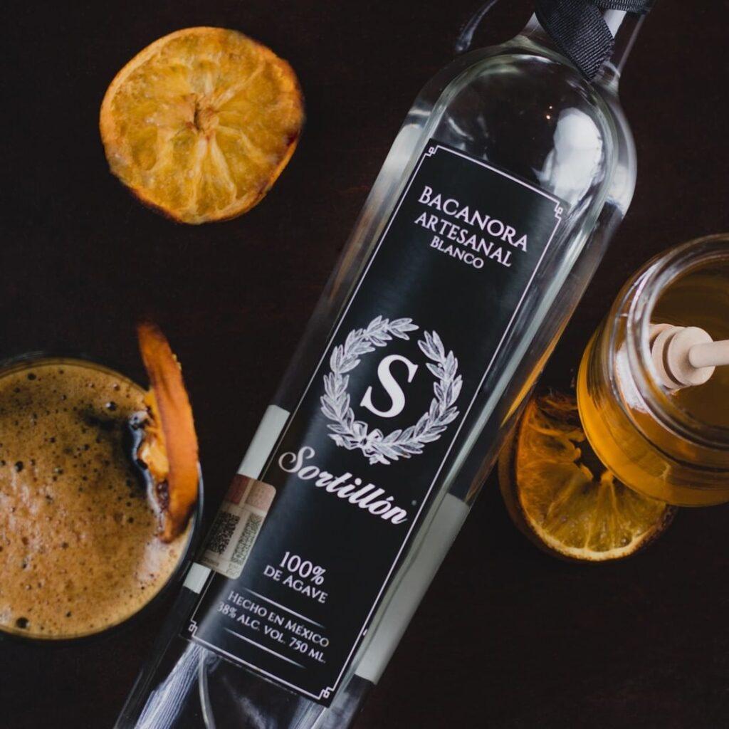Botella transparente con etiqueta de fondo negro y letras color blanco. a los lados se encuentran naranjas horneadas con bebidas color miel.