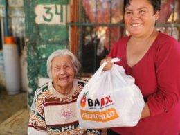 mujer de blusade manga larga roja sostiene bolsa de plástico con alimentos en el interior y a un costado una señora anciana sonríe