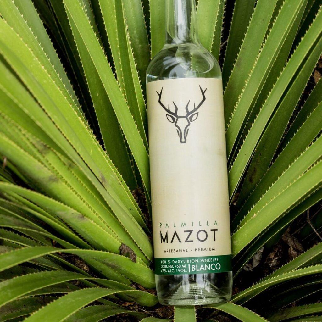 Botella transparente con etiqueta color crema. En la parte de arriba de la etiqueta en color negro esta una forma de un venado con cuernos. Debajo de la botella es una planta de agave color verde vivo.