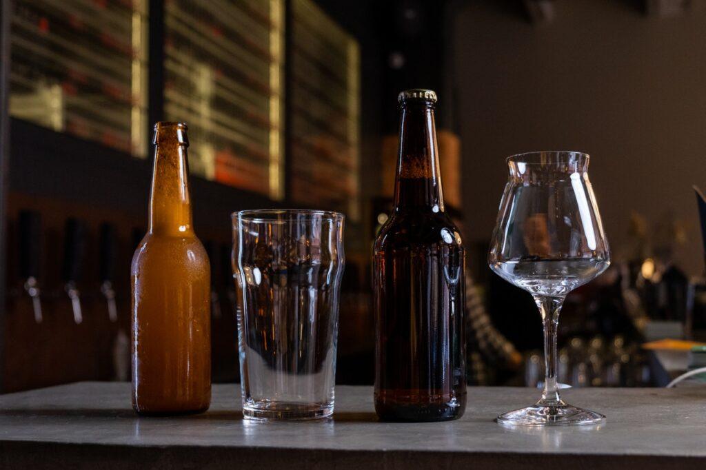 De lado derecho botella de cerveza color ambar, despues un vaso de cristal, enseguida otra botella de cerveza y al final una copa de vidrio.