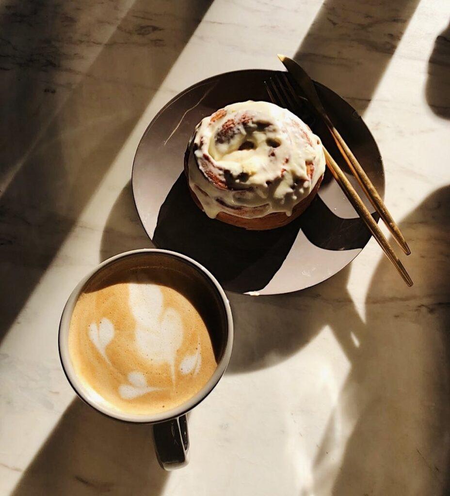 paza de café con una dona glaseada a un lado