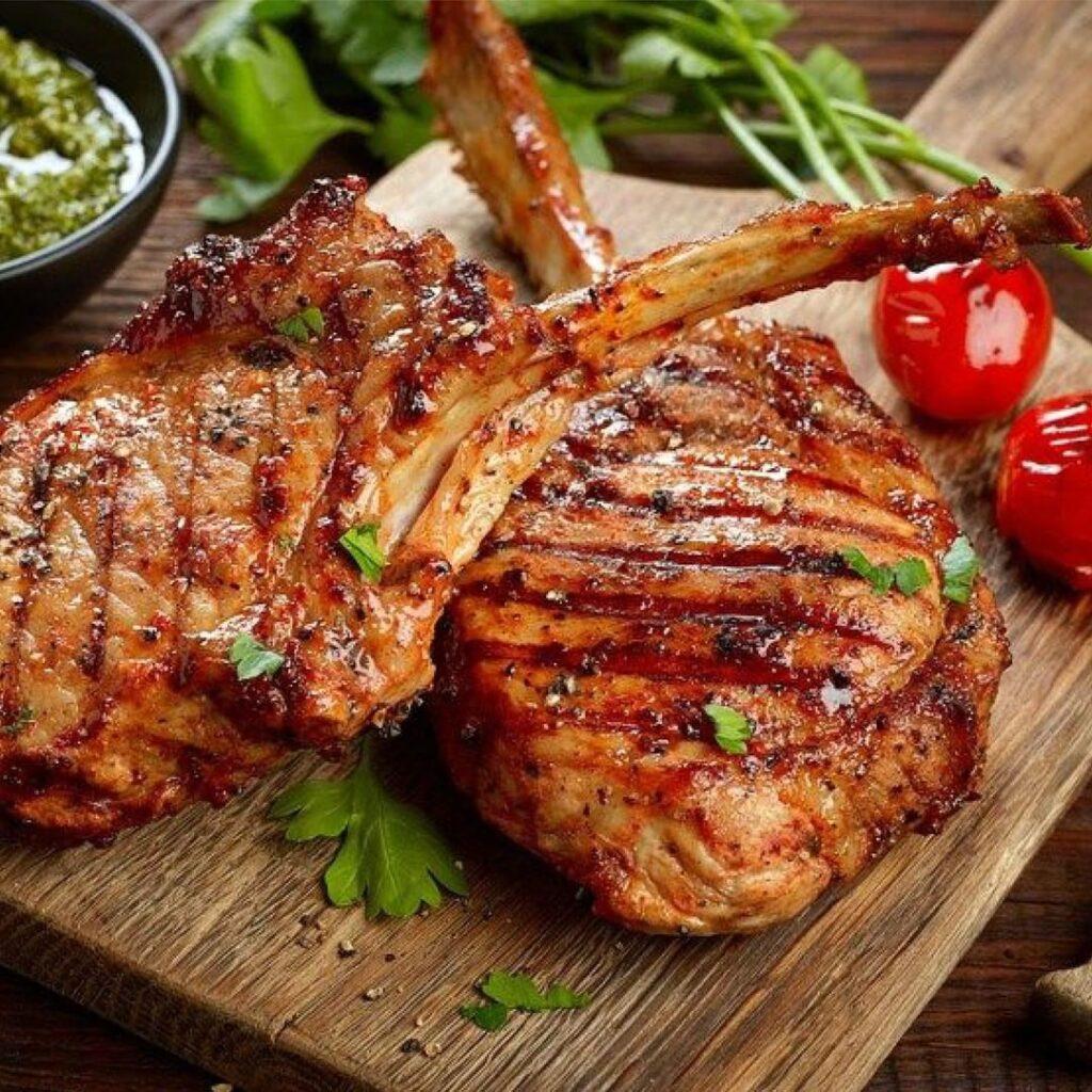 Dos bistec de cerdo asados, en una tabla de picar de madera junto a tomatillos cherry color rojo y un poco de cilantro.