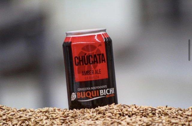 Lata de cerveza color negro con rojo, la parte de abajo Buqui con letras color naranja y Bichi con letras color blanco