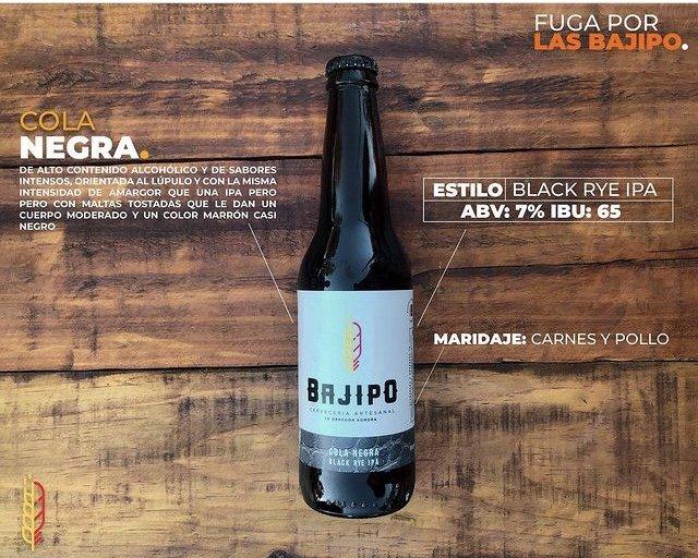 Botella de cerveza de vidrio color ambar con etiqueta color blanca, con letras color negro dice BAJIPO, de fondo mesa color cafe claro y oscuro.
