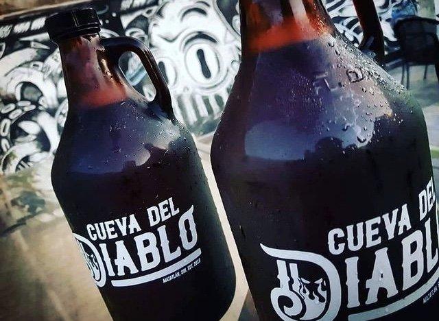 Botella color ambar con letras color blanco que dicen cueva del diablo. Cervezas Artesanales