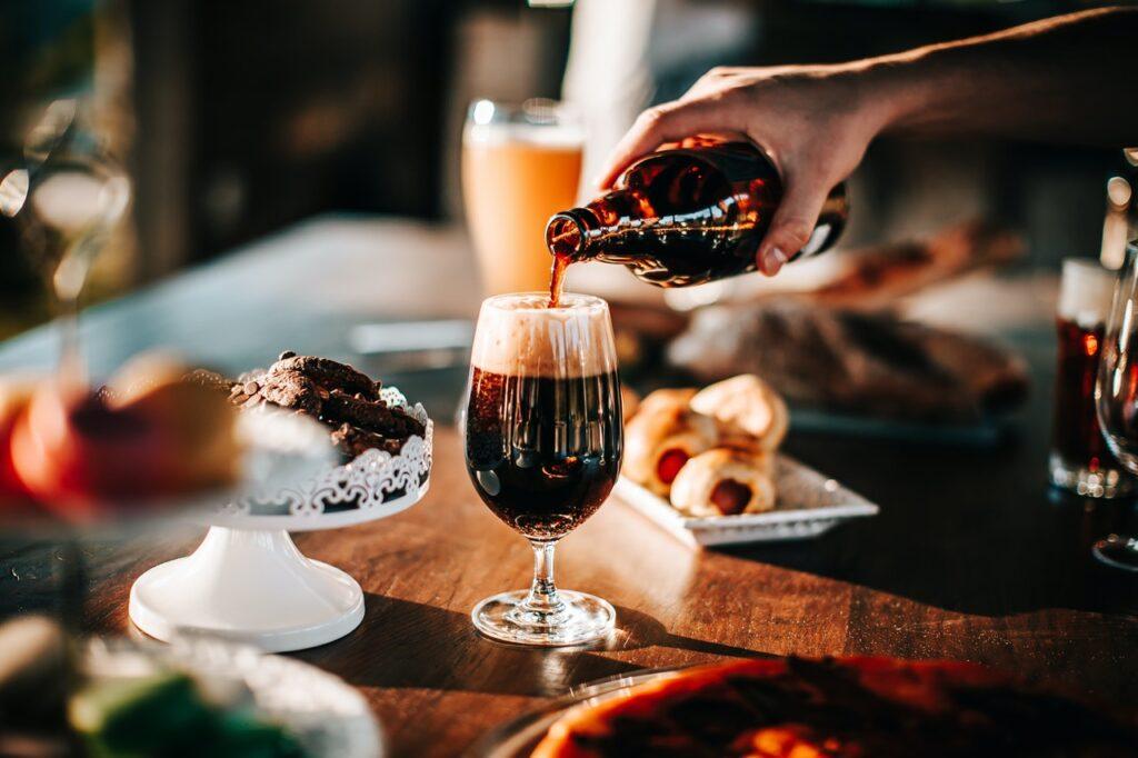 Copa de cerveza en una mesa, mano derecha sirviendo de una botella color ambar