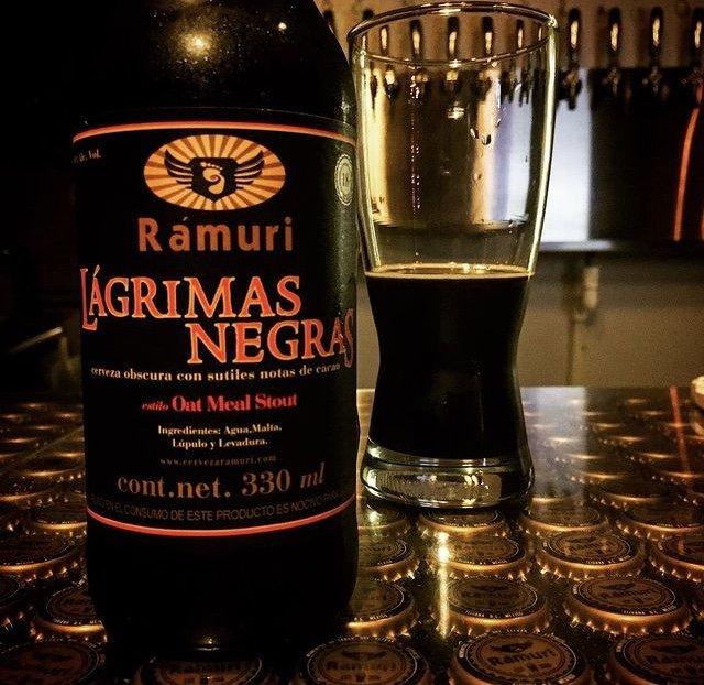 """Vaso menos de la mitad con cerveza muy oscura, al lado izquierdo una botella color negro con letras color rojo """"lagrimas negras"""". Cervezas artesanales"""