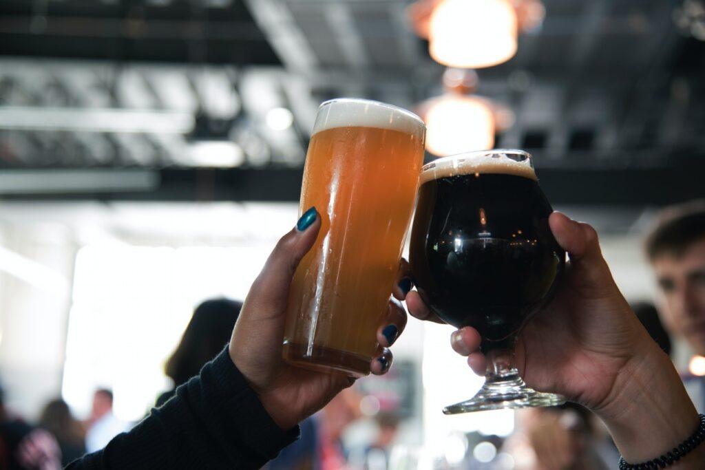 Manos con vaso y copa llena de cerveza, mano derecha cerveza oscura y mano izquierda cerveza clara.