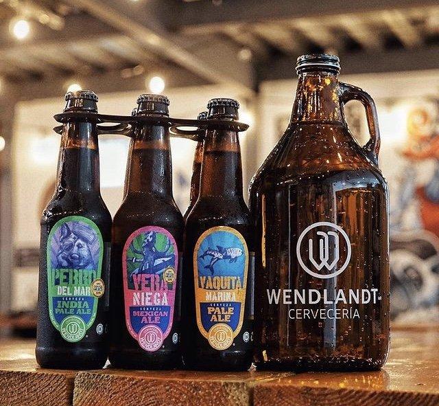 Botellas de cerveza color ambar, tres son medias y en la parte derecha es un galon de vidrio color ambar.
