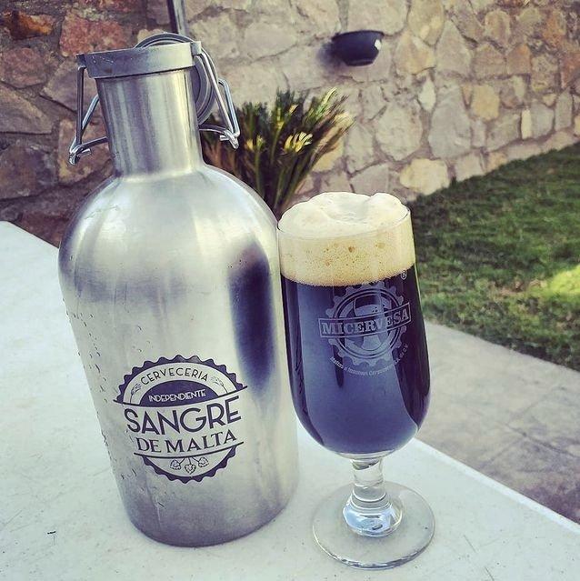 En la parte izquierda una botella grande de acero inoxidable con logotipo de letras color negro, en el lado derecho una copa grande con cerveza oscura.