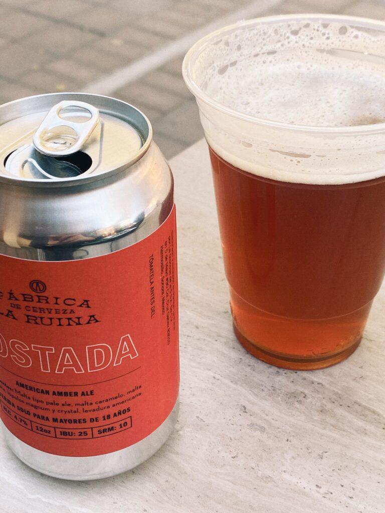 A la izquierda: una lata de cerveza color plateada con etiqueta color naranja ladrillo. A la derecha: vaso de plástico transparente llena de cerveza oscura.