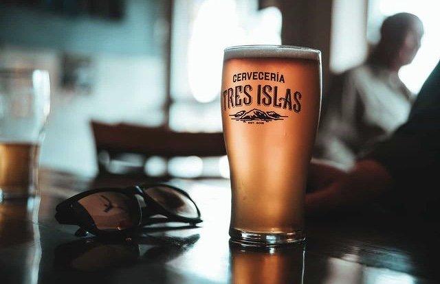 Vaso grande de cerveza color ambar, a un lado unos lentes color negro.