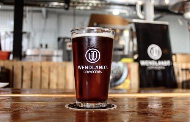 Vaso de cerveza color oscura en un vaso de vidrio con letras color blancas, de fondo una mesa color cafe.