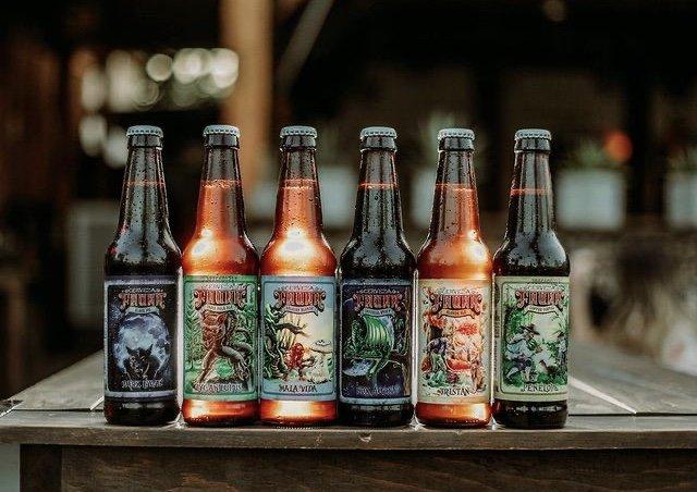 sietes botellas color ambar de cerveza encima de una mesa color cafe oscura